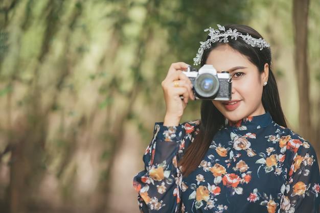 Portrait de femme asiatique est un photographe professionnel avec appareil photo sans miroir