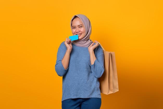Portrait d'une femme asiatique excitée tenant un sac à provisions et une carte de crédit mordante sur fond jaune