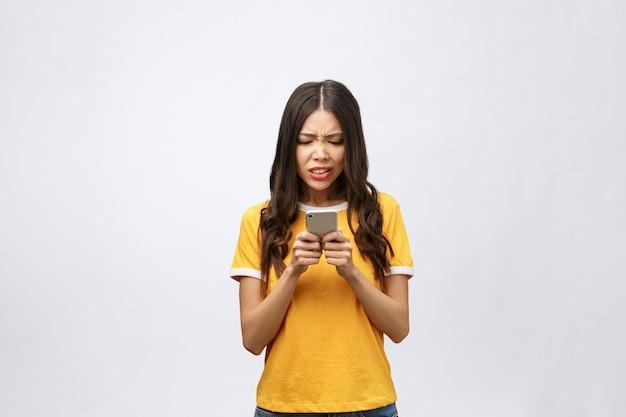 Portrait d'une femme asiatique furieuse parlant sur mobile