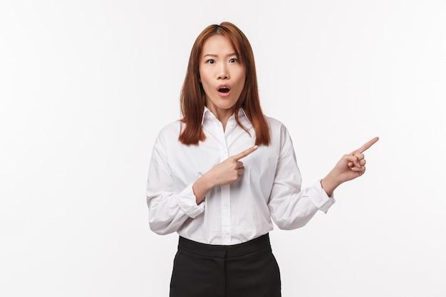 Portrait de femme asiatique gaie impressionnée en chemise blanche, pointant les doigts vers la droite comme parler de nouvelles géniales, promotion de nouveaux produits, discuter de potins, amusé, mur blanc