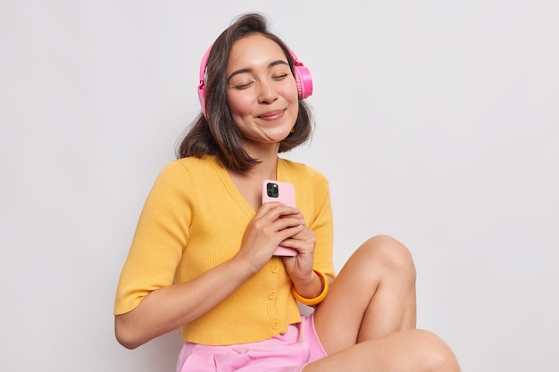 Portrait d'une femme asiatique heureuse aux cheveux noirs apprécie la musique préférée un son parfait dans des écouteurs sans fil tient un cellulaire moderne garde les yeux fermés porte des vêtements décontractés isolés sur un mur blanc