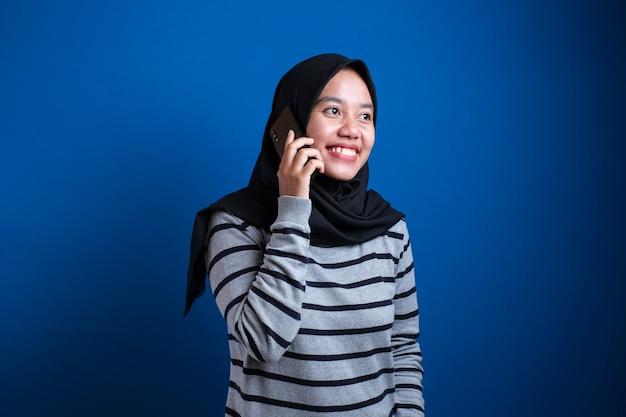 Portrait d'une femme asiatique heureuse portant le hijab appelant avec un téléphone portable sur fond bleu