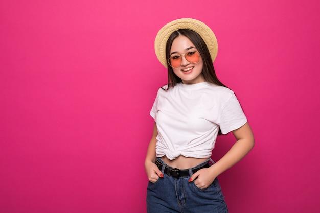 Portrait d'une femme asiatique joyeuse sur mur rose