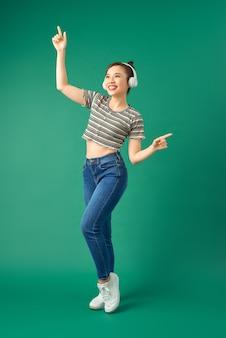 Portrait de femme asiatique joyeuse sur des vêtements décontractés dansant et écoutant de la musique avec un casque sur vert.