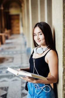 Un portrait d'une femme asiatique avec livre étudiant sur le campus