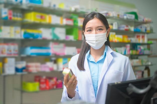 Un portrait de femme asiatique pharmacien portant un masque chirurgical dans une pharmacie moderne