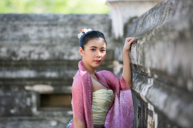 Portrait d'une femme asiatique portant des vêtements traditionnels thaïlandais lanna et shan debout près d'un mur