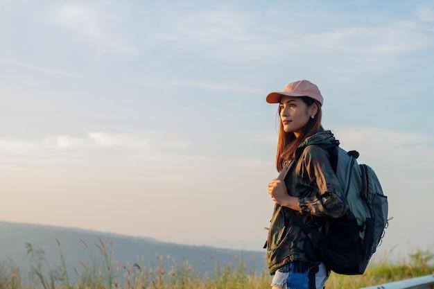 Portrait femme asiatique randonnée. elle souriait et était heureuse de voyager au lever du soleil au sommet de la montagne