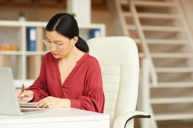 Portrait de femme asiatique réussie travaillant au bureau dans un intérieur de bureau moderne, espace copie