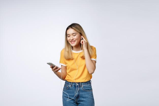 Portrait d'une femme asiatique satisfaite joyeuse au casque d'écoute de la musique et de sauter