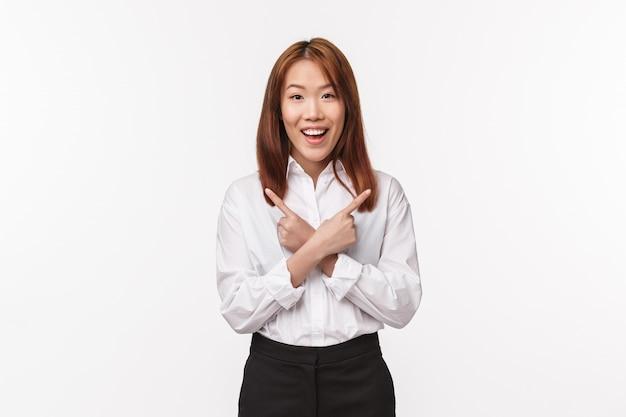 Portrait de femme asiatique souriante heureuse, employé de bureau en chemise blanche, pointant les doigts sur le côté gauche et droit à deux choix, quelques variantes, demandant des conseils, regardez joyeux sur le mur blanc