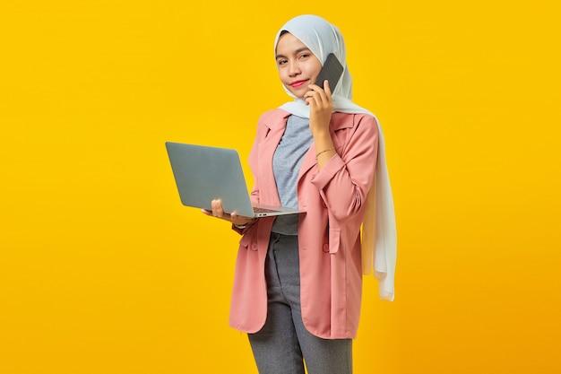 Portrait d'une femme asiatique souriante et parlant sur un smartphone tout en tenant un ordinateur portable argenté isolé sur fond jaune