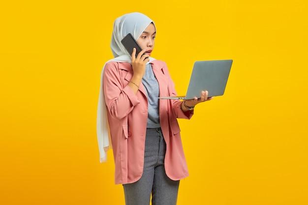 Portrait d'une femme asiatique surprise et choquée parlant sur un smartphone tout en tenant un ordinateur portable argenté isolé sur fond jaune