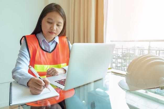 Portrait femme asie ingénieur écrit note sur son cahier au site de contruction.