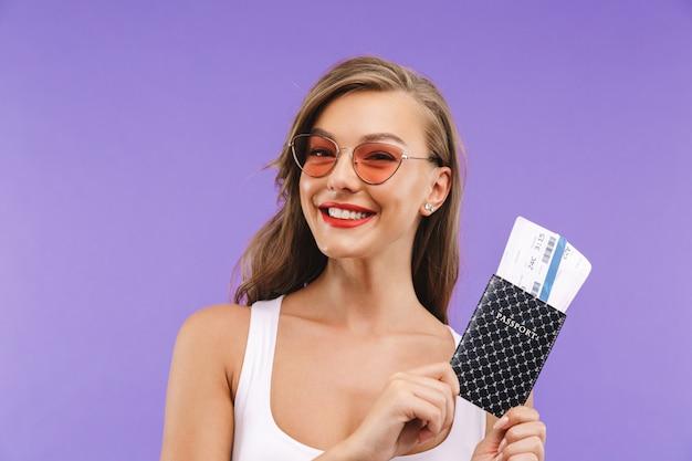 Portrait de femme assez heureuse en vêtements d'été et lunettes de soleil souriant et tenant un passeport et des billets de voyage,