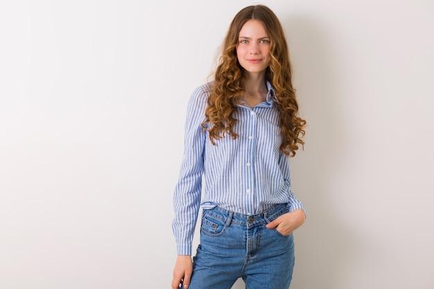 Portrait de femme assez naturelle ypung posant en chemise en coton rayé bleu contre blanc