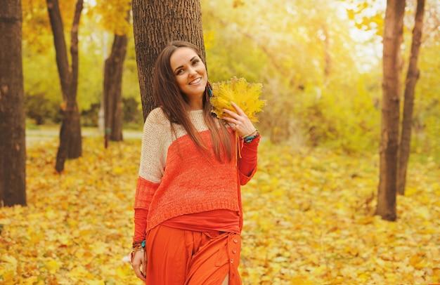 Portrait de femme assez souriante, marchant dans un parc en automne, vêtue d'un pull et d'une jupe orange décontractés
