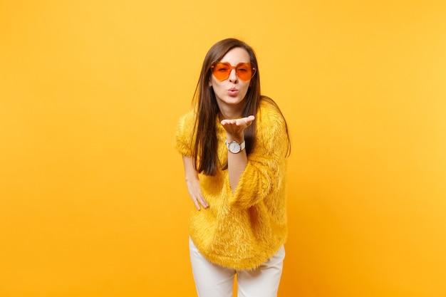 Portrait d'une femme assez tendre en pull de fourrure, lunettes coeur orange soufflant sur les lèvres, envoyant un baiser d'air isolé sur fond jaune vif. les gens émotions sincères, concept de style de vie. espace publicitaire.