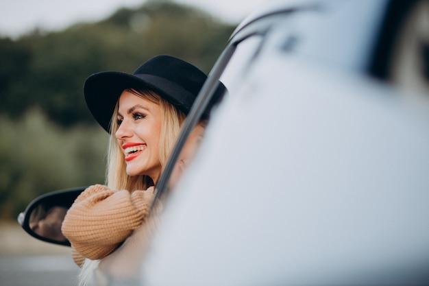 Portrait de femme assise dans la voiture et regardant par la fenêtre