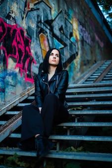 Portrait de femme assise sur un escalier du soir