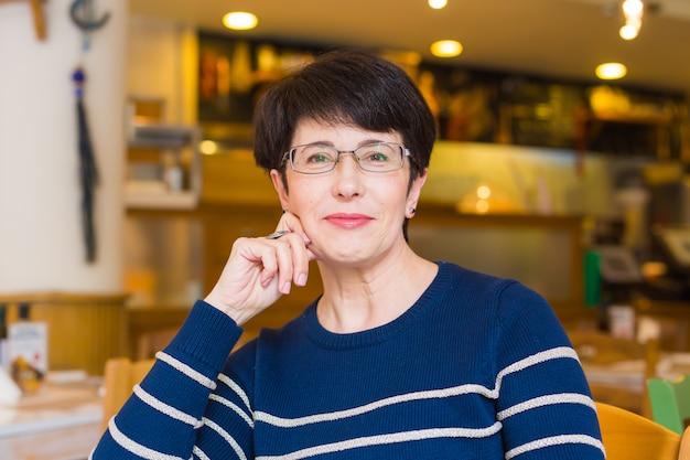 Portrait de femme assise à table au café.