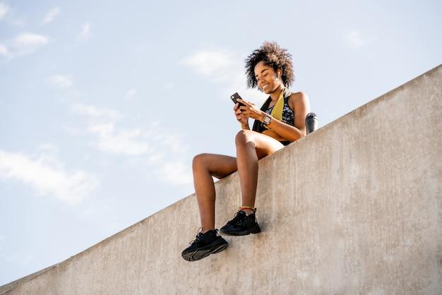 Portrait de femme athlète afro à l'aide de son téléphone portable et se détendre après un entraînement à l'extérieur