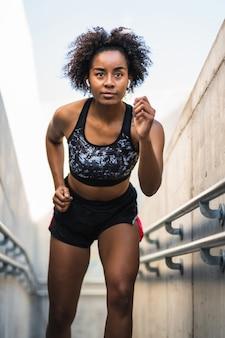 Portrait de femme athlète afro en cours d'exécution et faire de l'exercice à l'extérieur