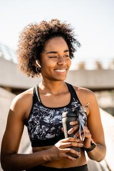 Portrait de femme athlète afro tenant une bouteille d'eau et se détendre après un entraînement à l'extérieur
