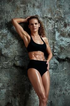 Portrait de femme athlétique caucasien fit attrayant habillé en haut et leggins, contre fond de mur de pierre sport, fitness, crossfit