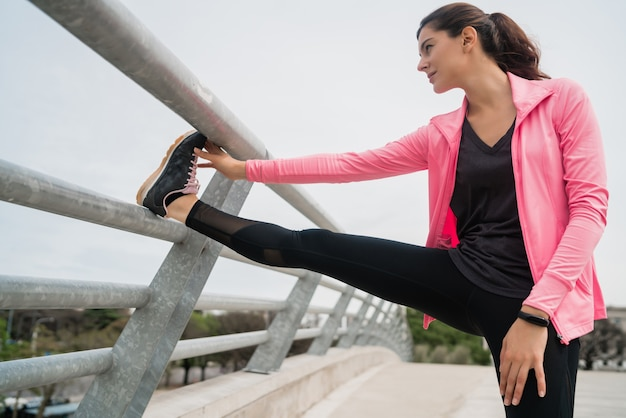 Portrait d'une femme athlétique qui s'étend des jambes avant de faire de l'exercice à l'extérieur. sport et mode de vie sain.