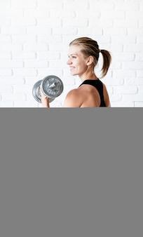Portrait de femme athlétique en vêtements de sport noir montrant ses muscles s'entraînant avec un haltère