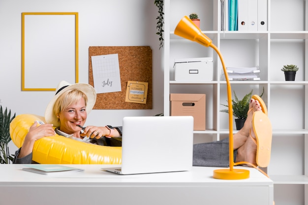 Portrait de femme au bureau préparée pour les vacances d'été