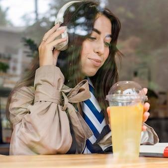 Portrait de femme au café avec de la limonade fraîche et des écouteurs