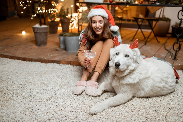 Portrait d'une femme au chapeau de noël avec son chien mignon célébrant les vacances du nouvel an, assis ensemble sur la terrasse joliment décorée de la maison