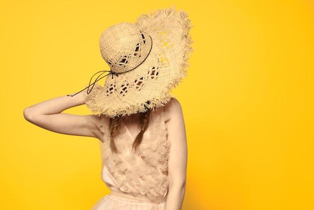 Portrait femme au chapeau de paille sur la vue recadrée jaune du modèle de robe d'été tresses romance.