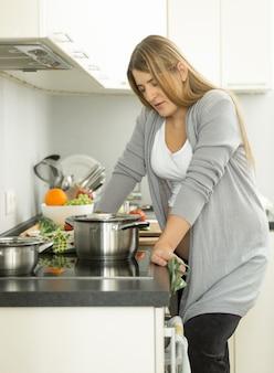 Portrait de femme au foyer épuisée posant dans la cuisine pendant la cuisson de la soupe