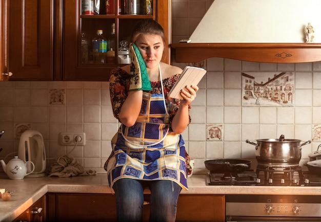 Portrait d'une femme au foyer étonnée à la recherche d'une recette sur une tablette alors qu'elle était assise sur une table