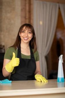 Portrait de femme au foyer heureuse dans la maison de nettoyage de gants en caoutchouc