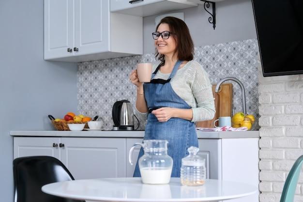 Portrait d'une femme au foyer mature dans un tablier à la maison dans la cuisine avec une tasse de thé, copyspace