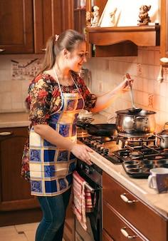 Portrait de femme au foyer mélange de soupe avec louche dans une casserole