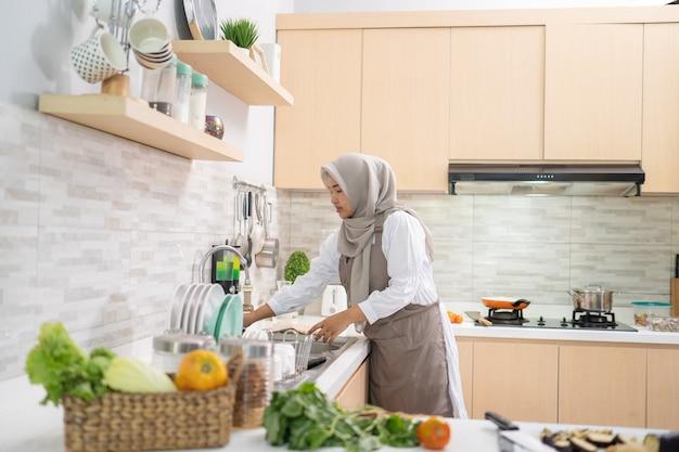 Portrait de femme au foyer musulmane se préparer à cuisiner dans la cuisine