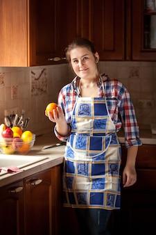Portrait de femme au foyer souriante tenant orange