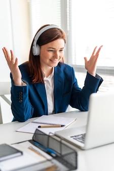 Portrait femme au travail ayant appel vidéo