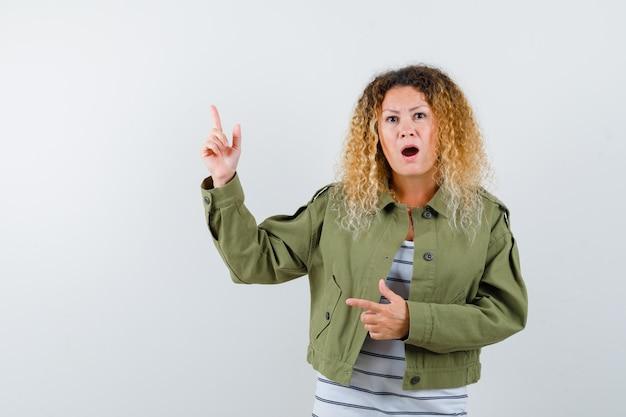 Portrait de femme aux cheveux blonds bouclés pointant vers le coin supérieur gauche en veste verte et à la vue de face confus