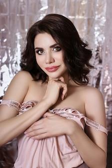 Portrait d'une femme aux cheveux bruns avec un beau maquillage professionnel sur un mur brillant. fille sexy avec une belle peau propre et un rouge à lèvres brillant sur ses lèvres