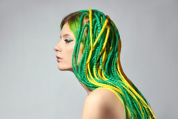 Portrait d'une femme aux cheveux de couleur créative de couleur verte et jaune.