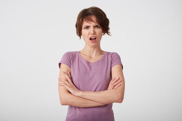 Portrait de femme aux cheveux courts mécontente en fronçant les sourcils en t-shirt blanc, indignée par une note d'examen trop basse, se dresse sur un mur blanc avec les bras croisés.