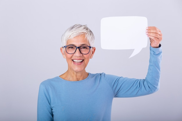 Portrait d'une femme aux cheveux gris mature excitée montrant une bulle de dialogue vide isolée sur un mur gris. personne agee, femme, tenue, bulle discours