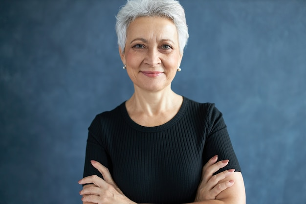 Portrait de femme aux cheveux gris à la mode à la retraite posant isolé en t-shirt noir gardant les bras croisés, étant de bonne humeur, regardant la caméra avec un sourire confiant, exprimant des émotions positives