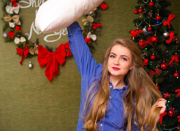 Portrait d'une femme aux lèvres rouge vif, cheveux longs blonds contre l'arbre du nouvel an. jeune, femme, blanc, oreiller, sien, mains